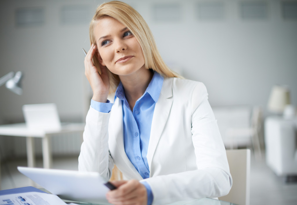 Young pensive businesswoman sitting at workplace in office