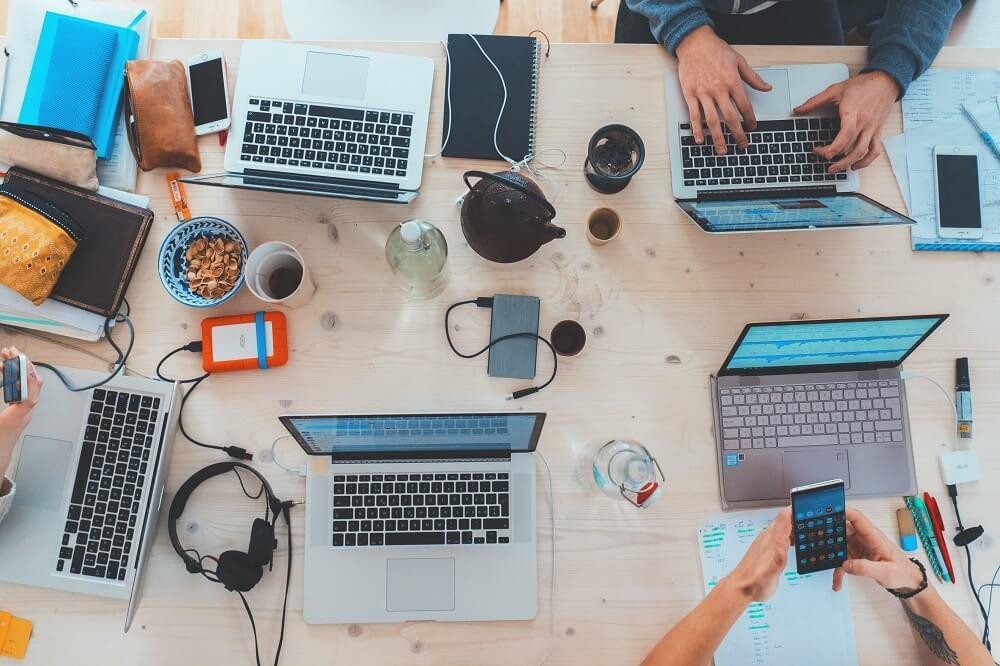 ひとつのテーブルでパソコンを並べて作業する人たち